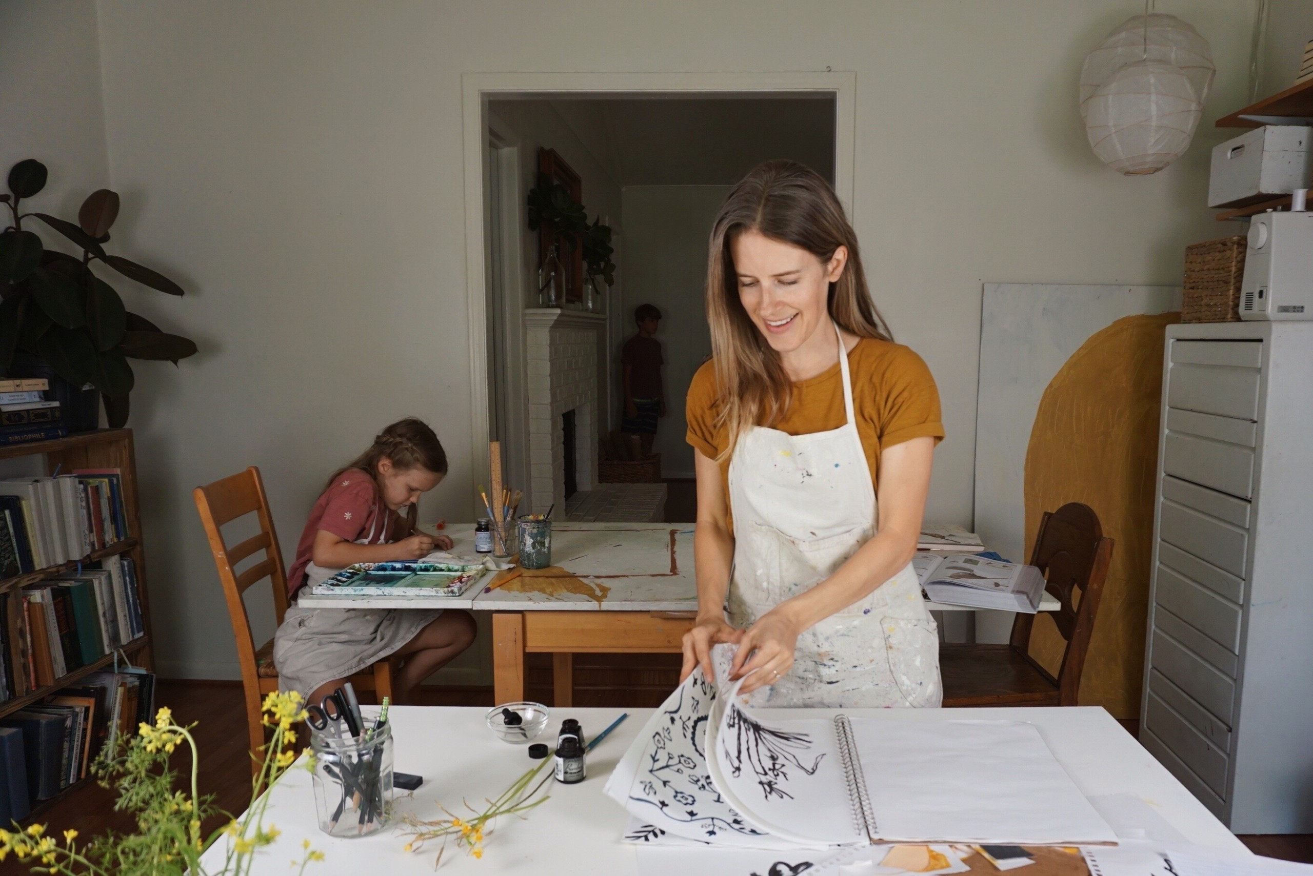 Rachel Smith works on a project. In the background, her daughter draws at a table.