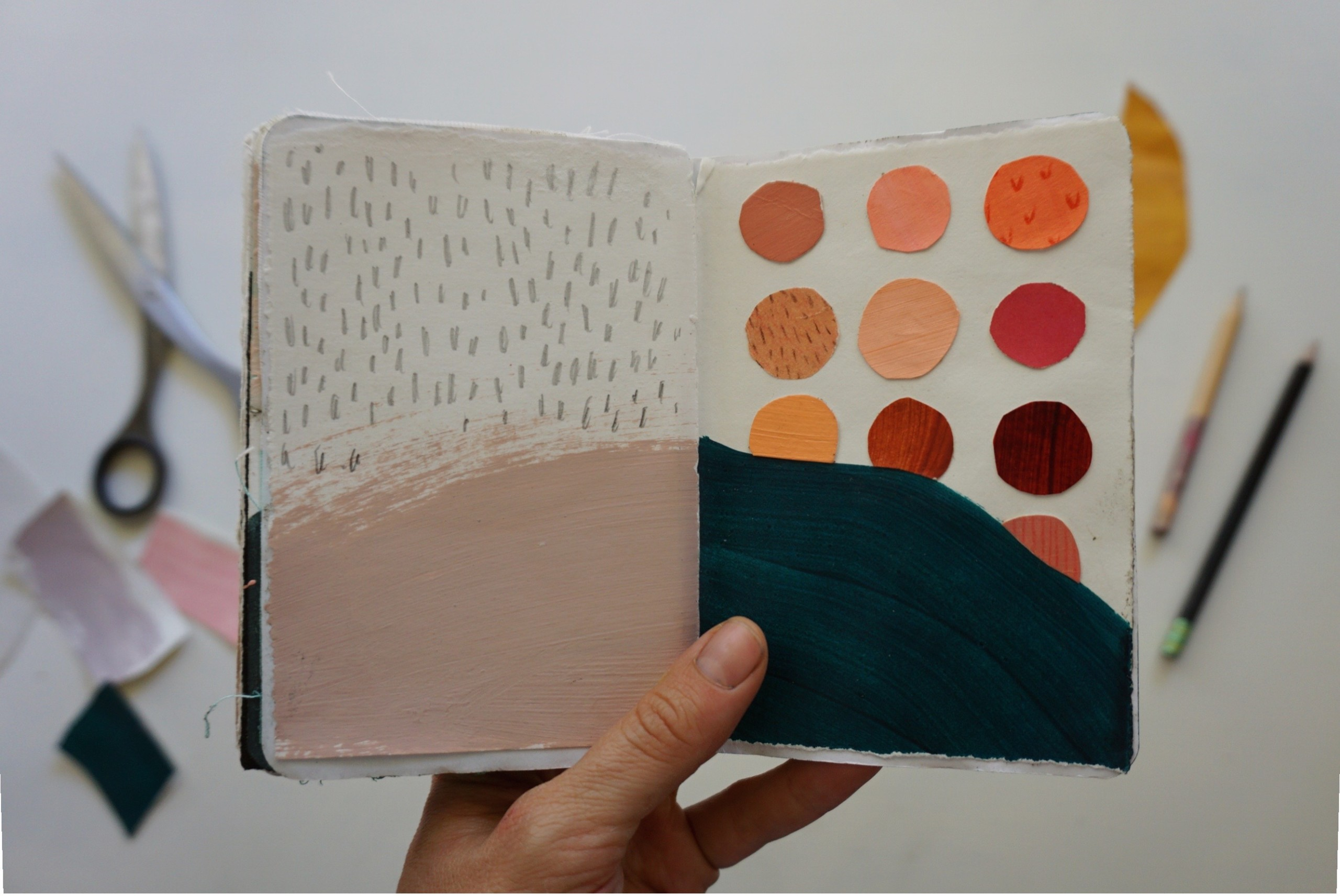 Rachel shows an open view of her sketchbook with painted and collaged shapes, as well as pencil-drawn marks.