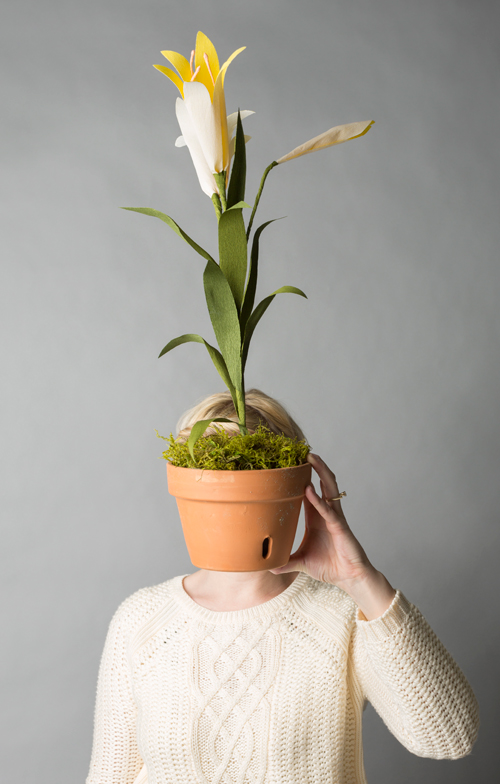 Brittany holds a paper easter lily in a terracotta pot in front of her face