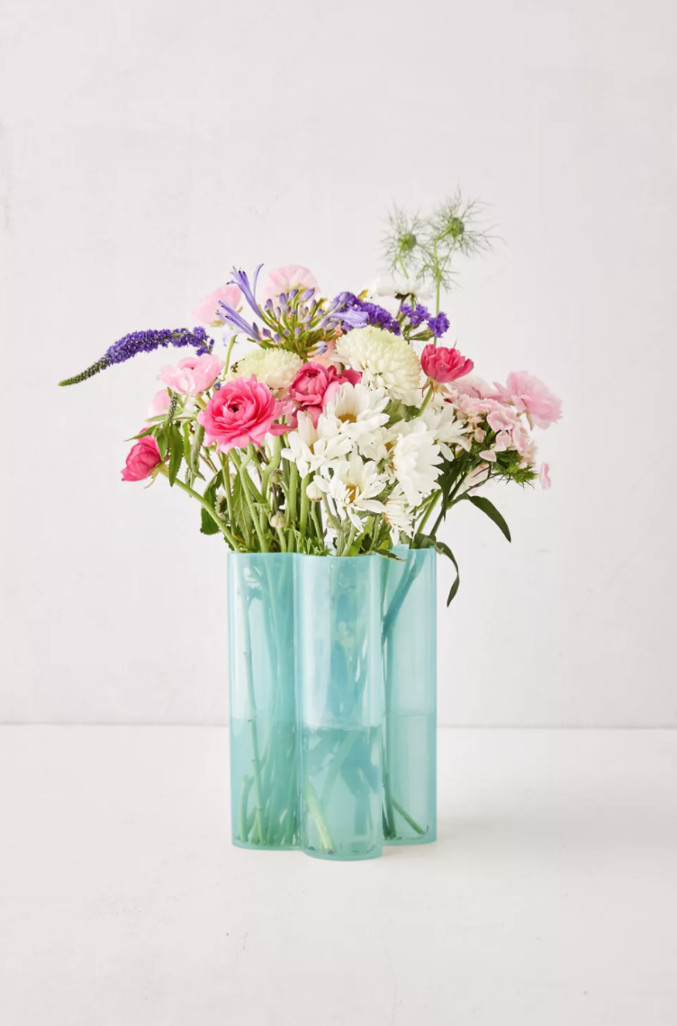 Pink, purple and white flowers burst out of a scalloped aqua vase