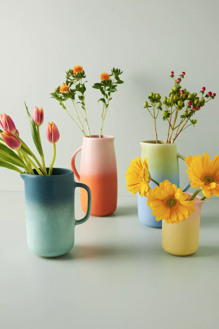 Fresh flowers in warm colors stick out of blue, pink, yellow, and aqua two-toned vases