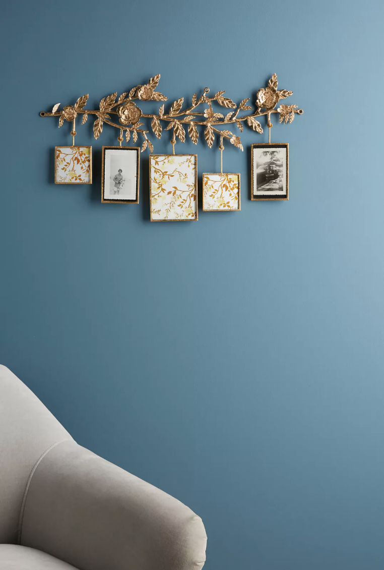A golden metal branch with intricate metal flowers and leaves and five hanging rectangular picture frames below in a powder blue room.