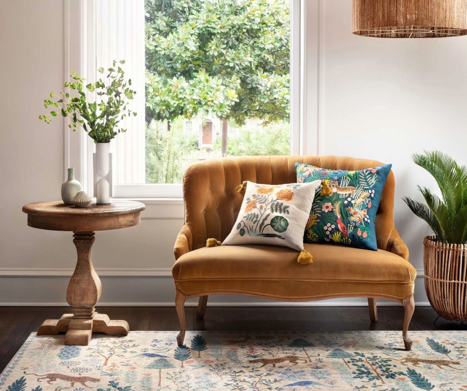 A cozy living room with wide open windows, lovely wooden furniture, a comfy loveseat, and floral throw pillows