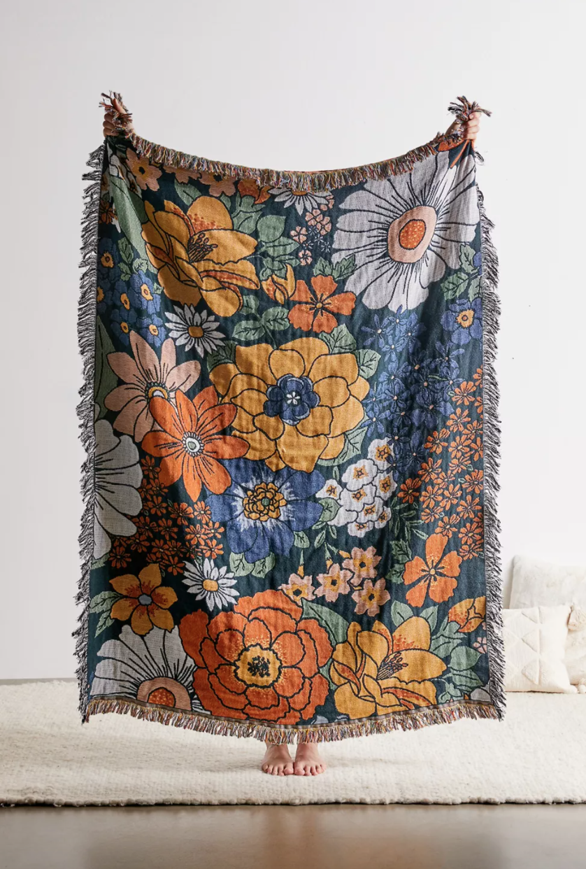 Someone stands behind a bold-printed floral blanket in royal blue and rich yellows and oranges, holding it up. Their hands and feet are visible.