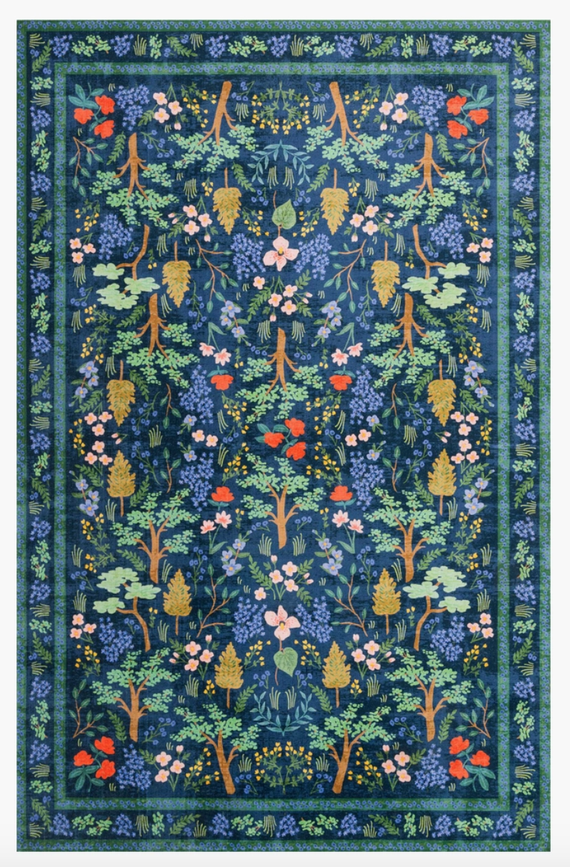 An intricately patterned rug in blues, greens, and pops of pinks, mustard, and pink.