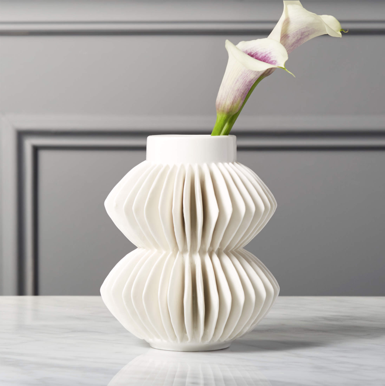 A white vase with ceramic, fan-like fins sits on a table. Two calla lilies are inside.