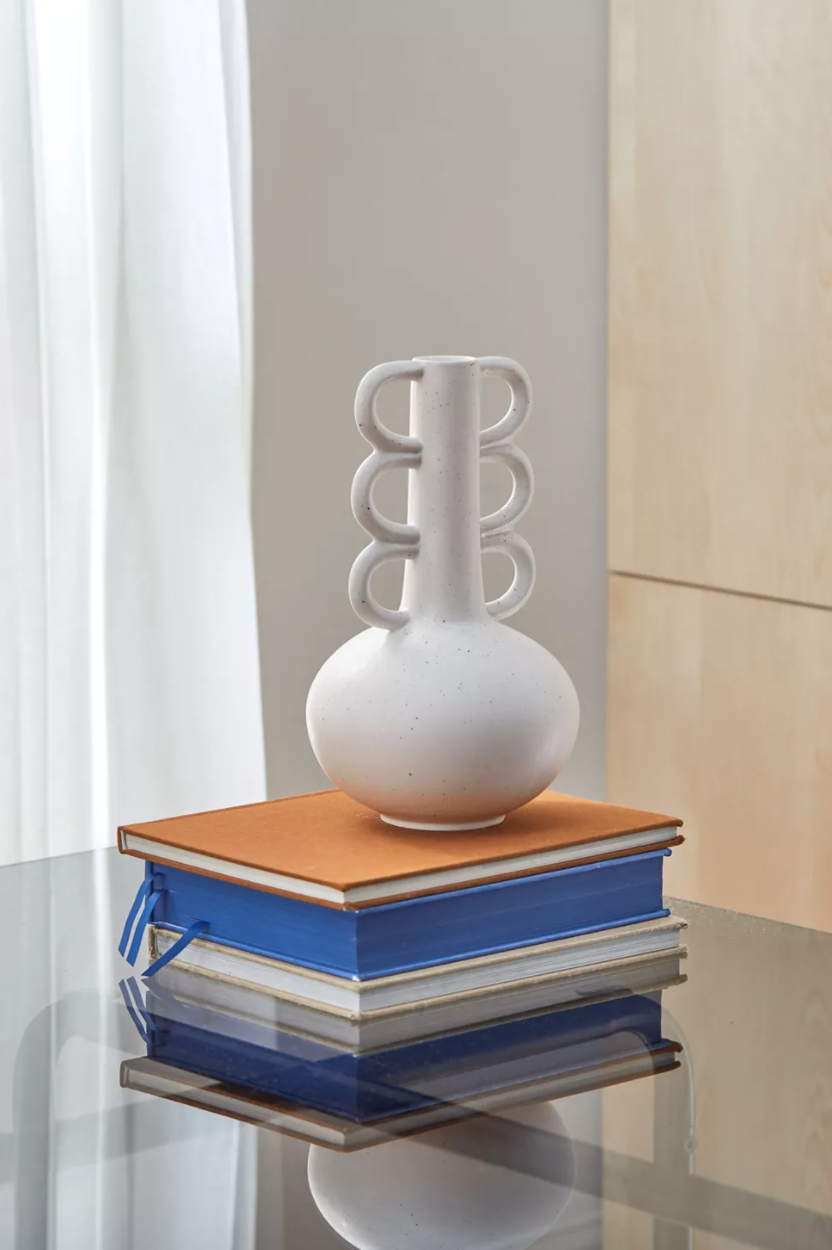 A vase with a tall neck and scalloped handles sits on a pile of books
