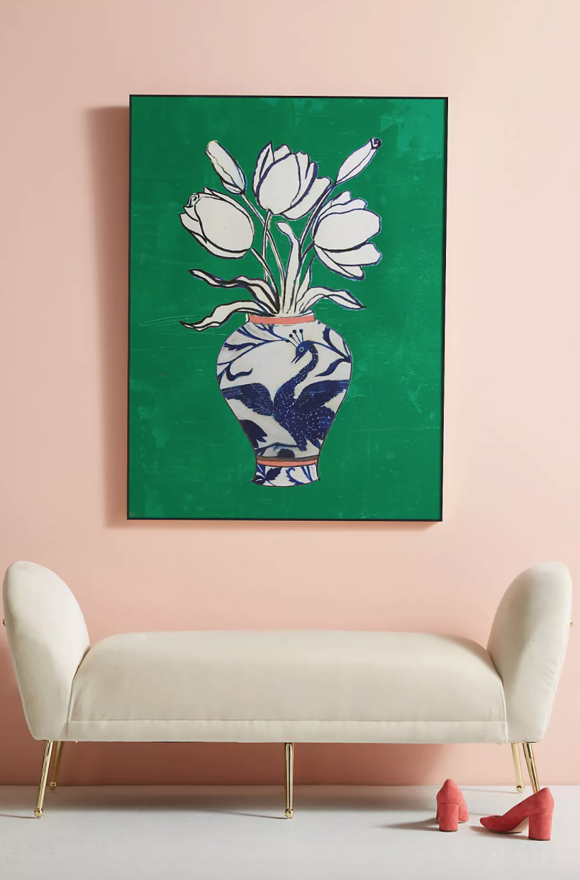 a bold green artwork on a blush pink wall over a white sofa