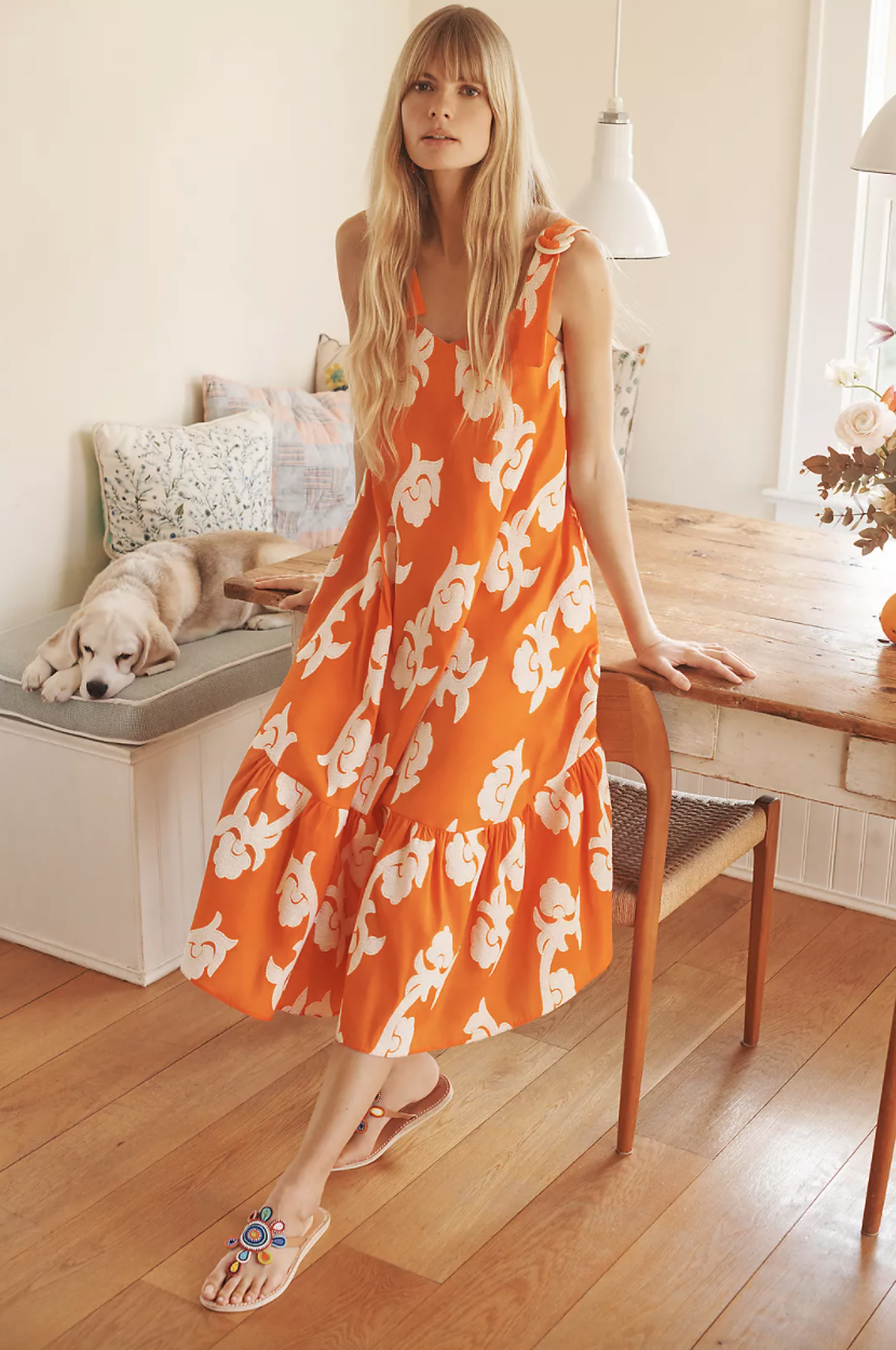 A woman leans against a chair in a light-filled room. She's wearing an orange sleeveless dress with a flounce at the bottom and abstract large white flowers printed on it. A dog lounges on a bench behind her.