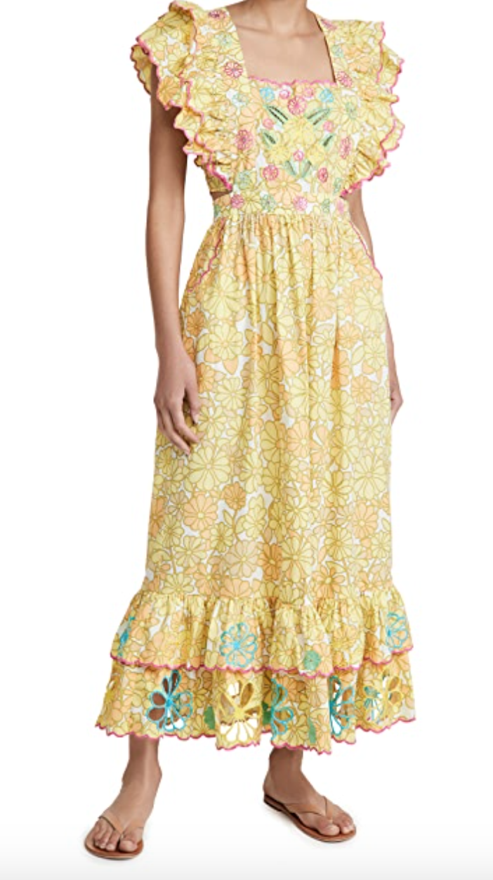 A woman wears a light yellow floral dress with Mexican-inspired embroidery and frilled sleeves with a flounce at the bottom.