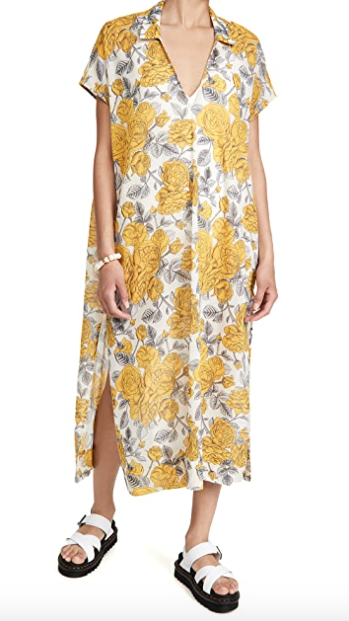 A woman wears a loose maxi dress in a shirt dress pattern. It's printed with large yellow flowers.