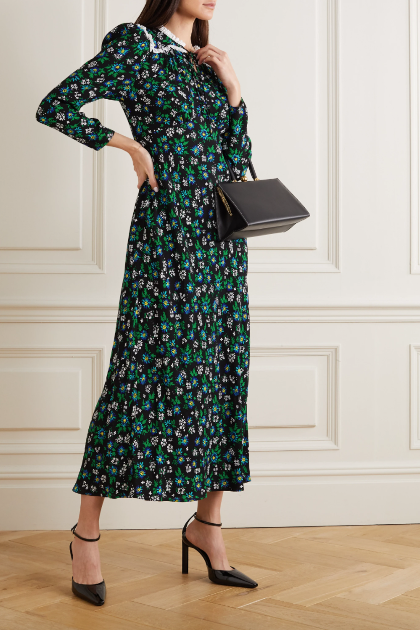 A woman wears a black and green floral printed midi dress with a lace-trimmed collar in a room with light wood floors.