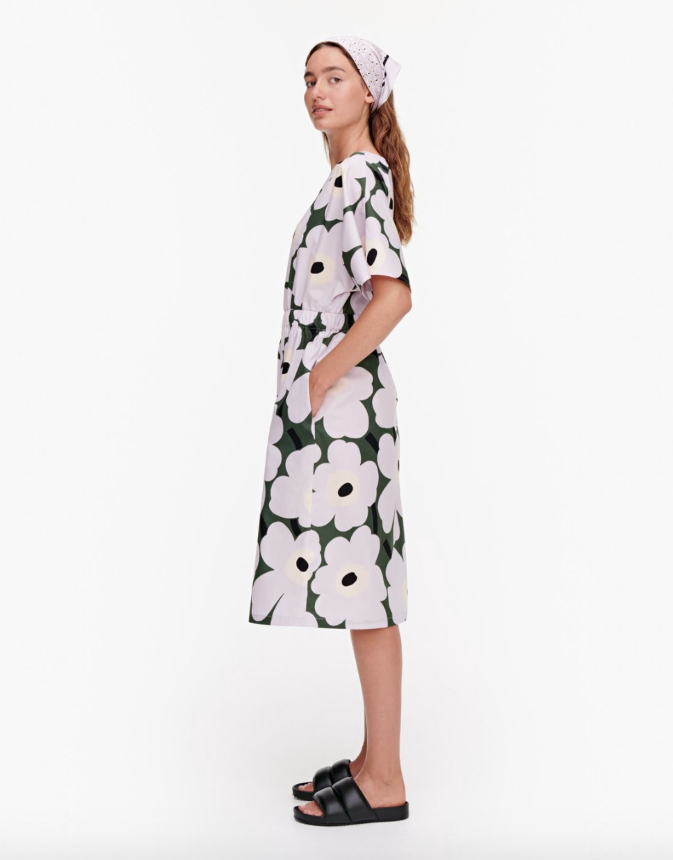 A woman wears a loose-fitting dress printed with green and purple large modern flowers.