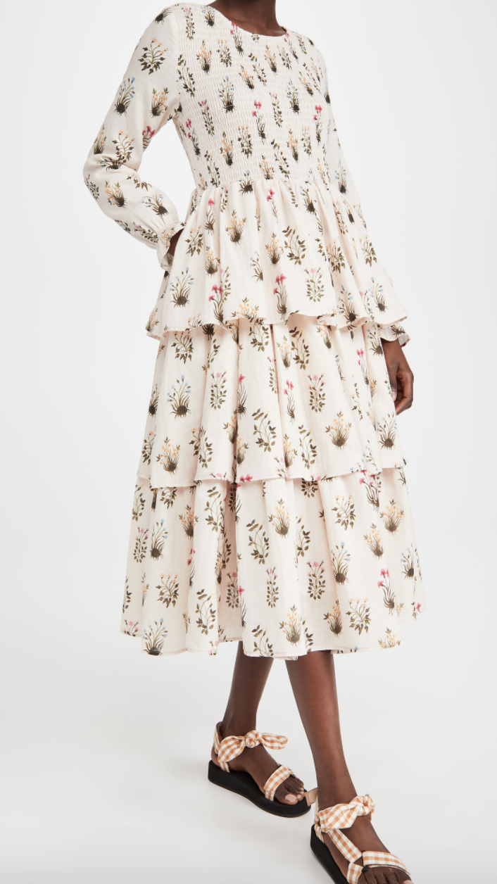 A woman wearing a cream-colored tiered dress with long sleeves and botanical illustrations printed on it.