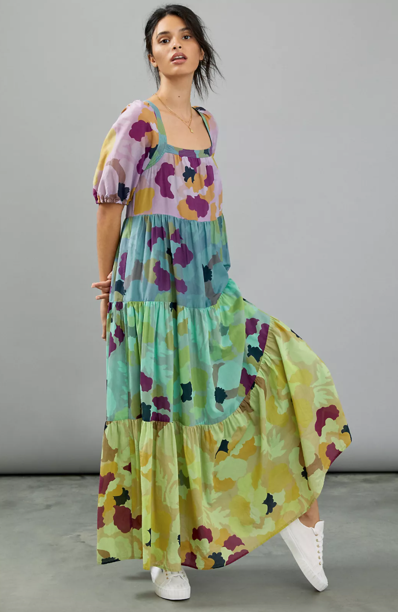 A woman wearing a tiered maxi dress with lilac, blue, aqua, and chartreuse floral tiers stands in a grey room