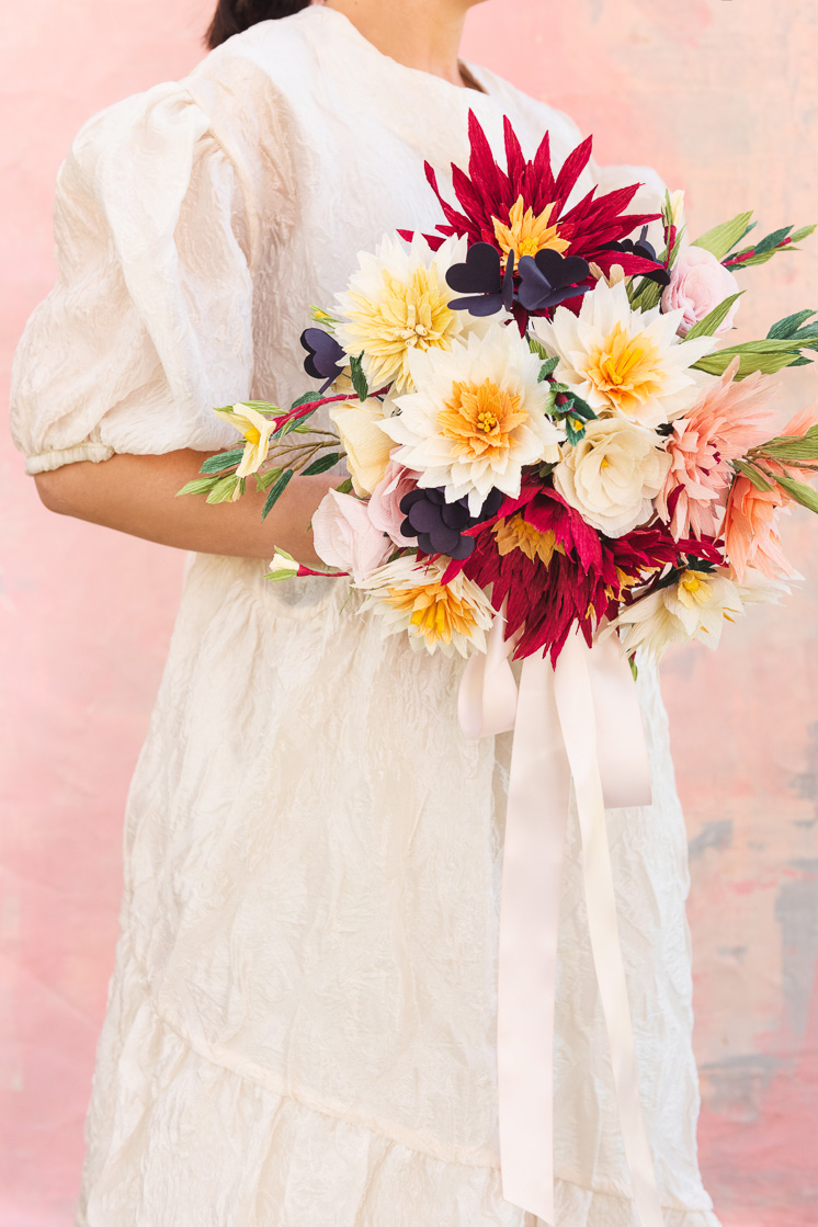 A bride in a white dress against a pink background holds a paper bouquet made of dahlias, roses, shamrocks, Mexican jasmine, and foliage.
