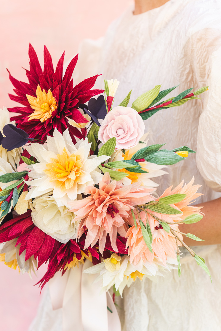 close up of a paper bouquet made of dahlias, roses, shamrocks, Mexican jasmine, and foliage.