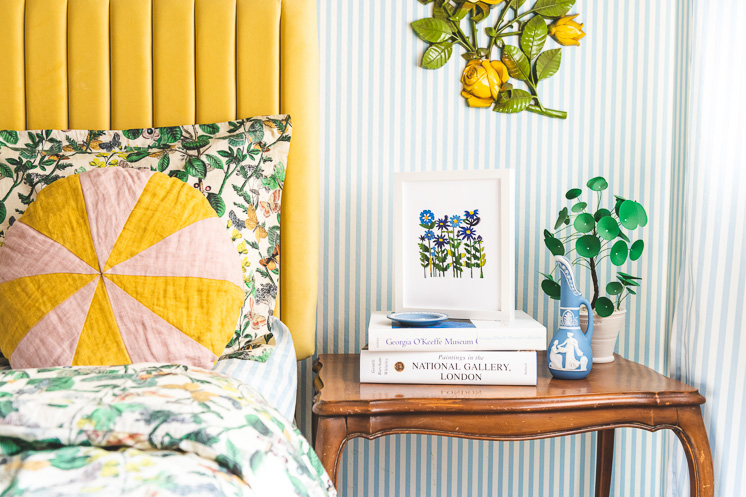 Field of Colored Flowers Papercut By Julie Marabelle is framed and perched on top of a stack of books next to a yellow bed and a blue and white striped wallpapered wall.