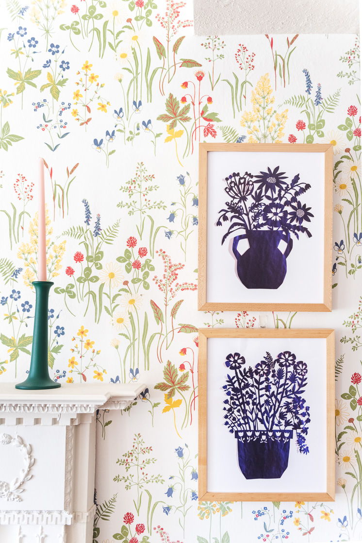 Two blue papercut art prints on a wildflower wallpaper wall next to a mantle with a green candlestick
