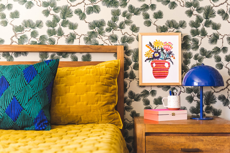 A framed paper-cut floral print on a spruce-themed wallpapered wall by a yellow bed and a blue lamp