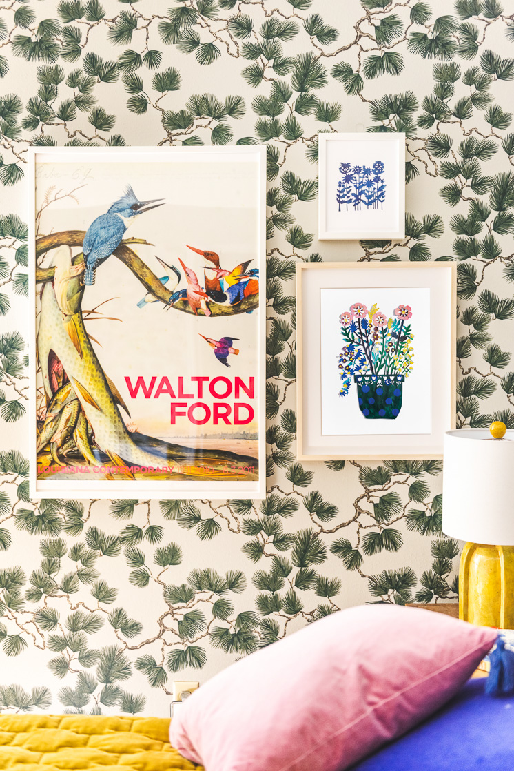 Two papercut floral prints on a spruce wallpapered wall.