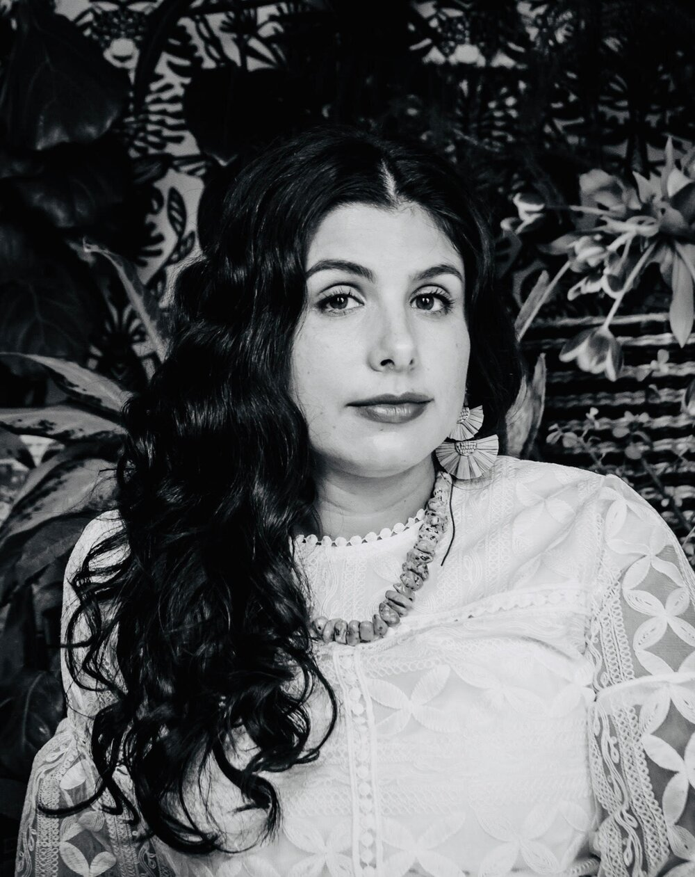 A black and white portrait of Michelle, who looks at the camera. She's wearing a white top and a chunky necklace, and she's standing in front of some plants