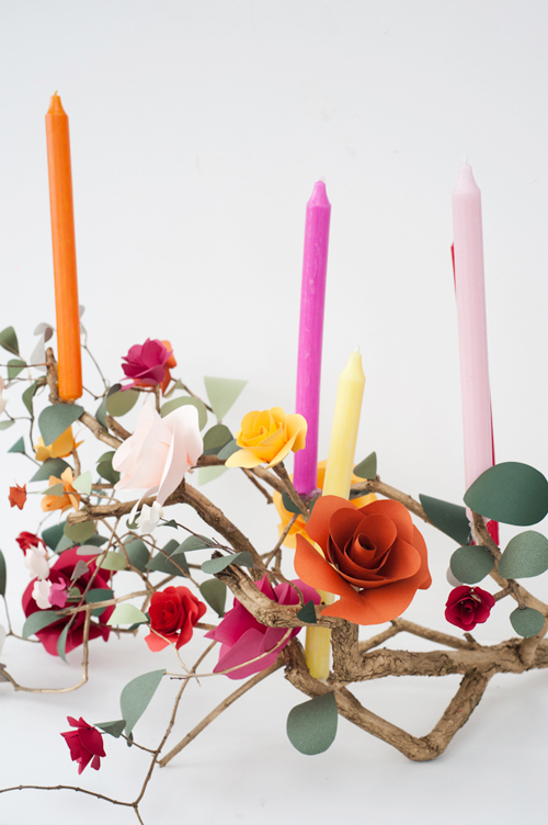Paper flowers and colorful candles on a branch