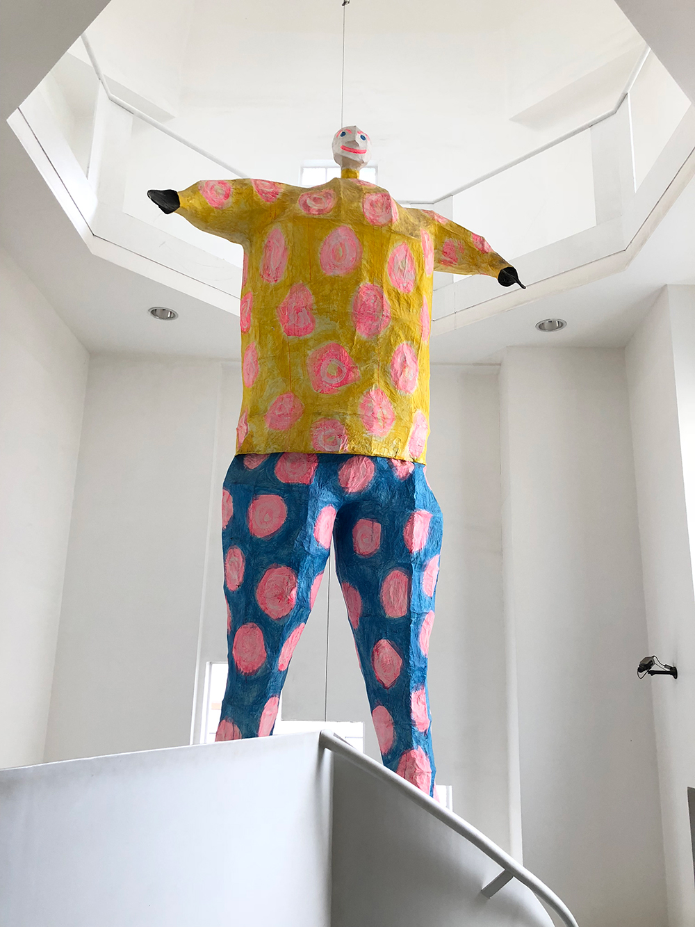 a colorful papier mache man floats in a white museum space