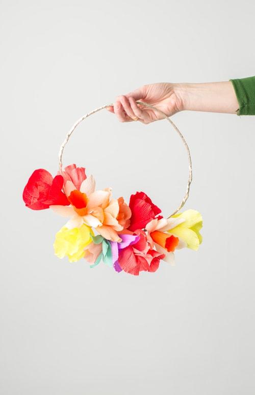 A hand reaches into frame holding a rainbow floral wreath