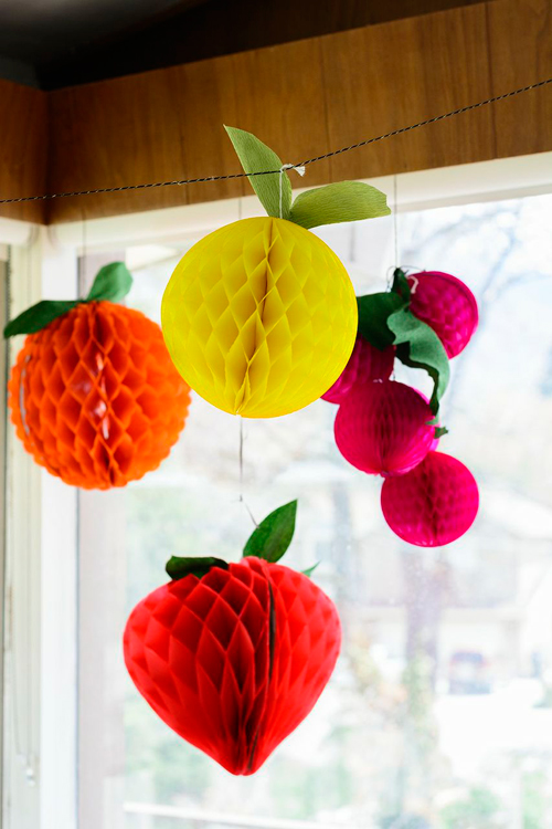paper fruits in the shape of grapes, an orange, a grapefruit, and a strawberry hang in front of a window