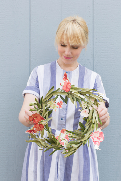 Brittany holding a wreath with floral accents cut from wallpaper.