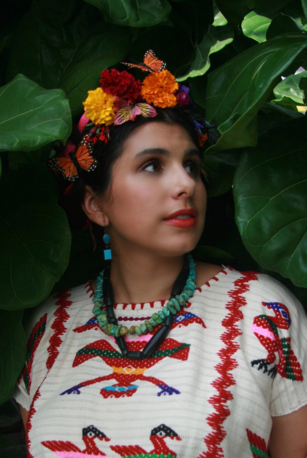 Michelle is wearing a traditional Mexican embroidered blouse and stone necklaces. She has flowers in her hair and is standing among leaves.
