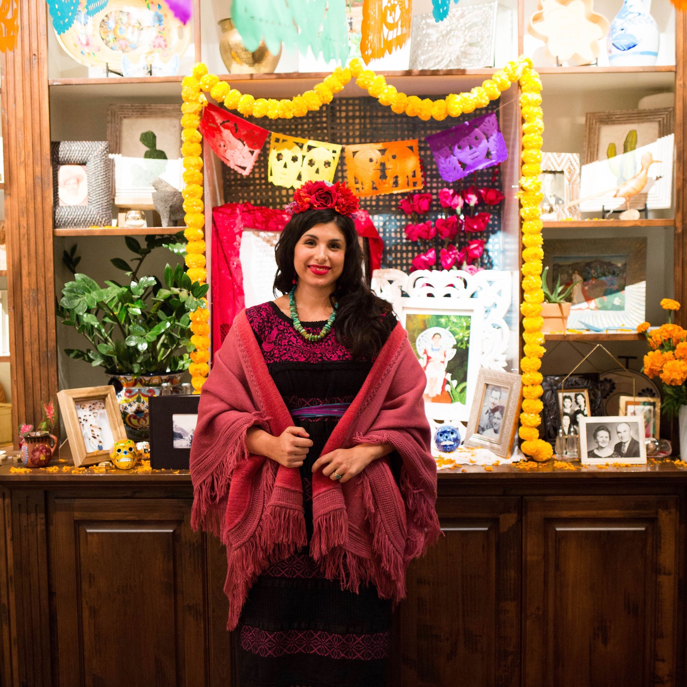 Michelle is wearing a red dress and rebozo. She has red flowers in her hair and she's standing in front of a Dia de los Muertos ofrenda.