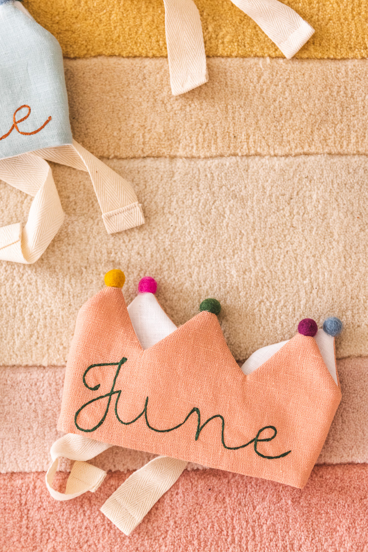 A pink Flower Lane crown embroidered with the name June  on a yellow, cream, and pink rug.