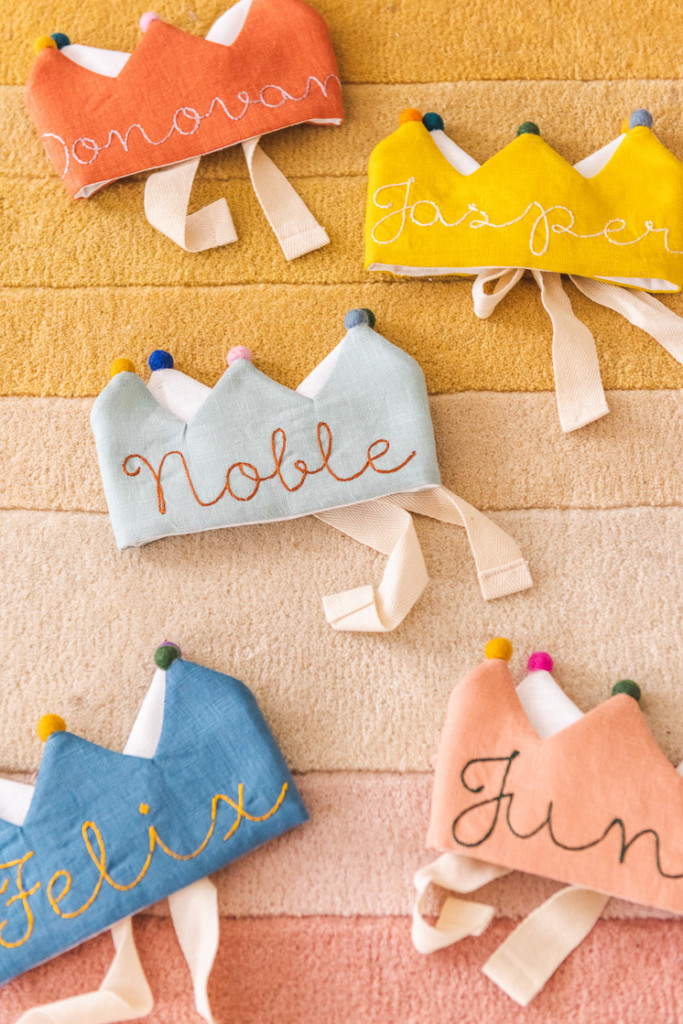 flower lane crowns in orange, yellow, pink, blue, and light blue on a yellow and pink background.
