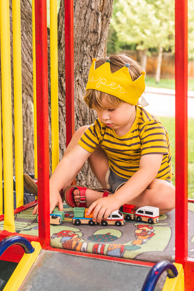 Jasper wears his yellow Flower Lane crown and plays with cars in a playground