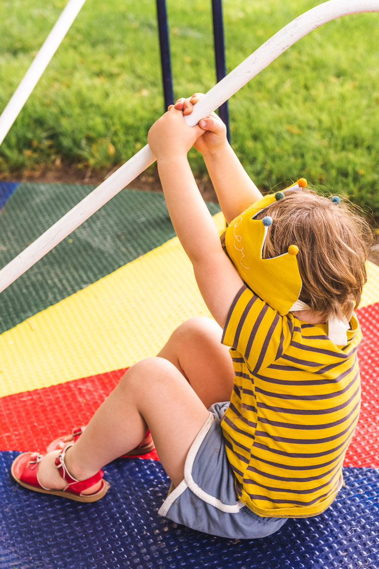 Jasper is wearing his yellow Flower Lane crown and a striped yellow shirt and playing on a playground.