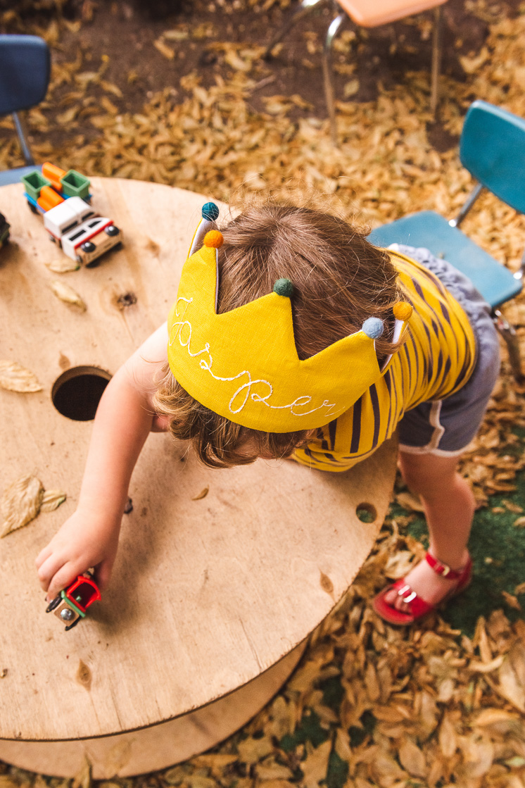 Jasper plays with toy cars at a playground. He's wearing his yellow Flower Lane crown