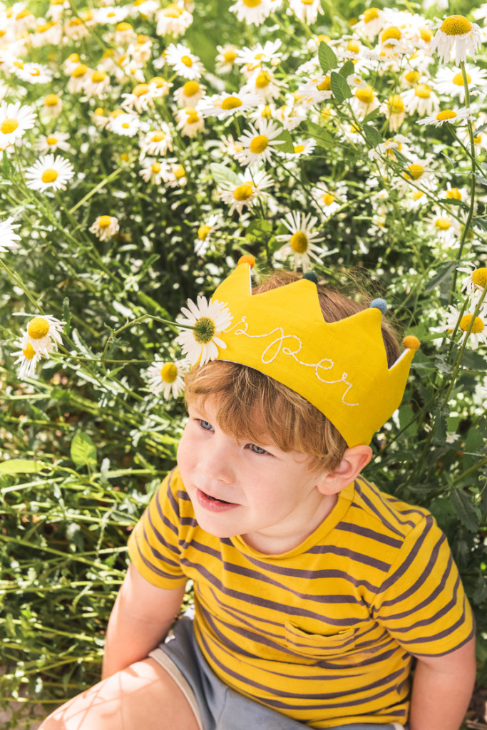 Jasper sits in a field of daisies wearing a yellow Flower Lane crown and a striped yellow shirt.