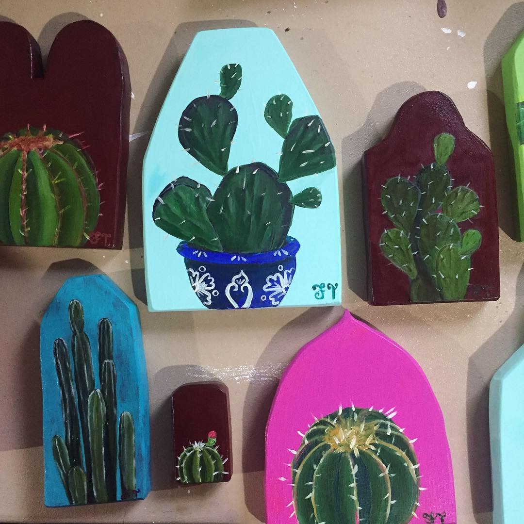 Paintings of cactuses against a white wall.