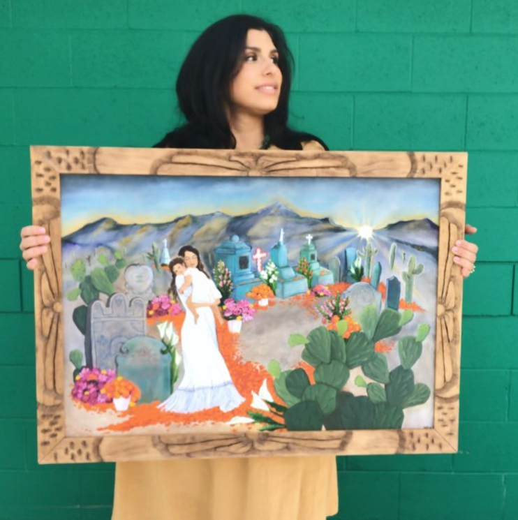 Michelle is holding up a painting of a woman holding a young girl in a Mexican cemetery surrounded by marigolds, nopales, and mountains. She's against a green brick wall.