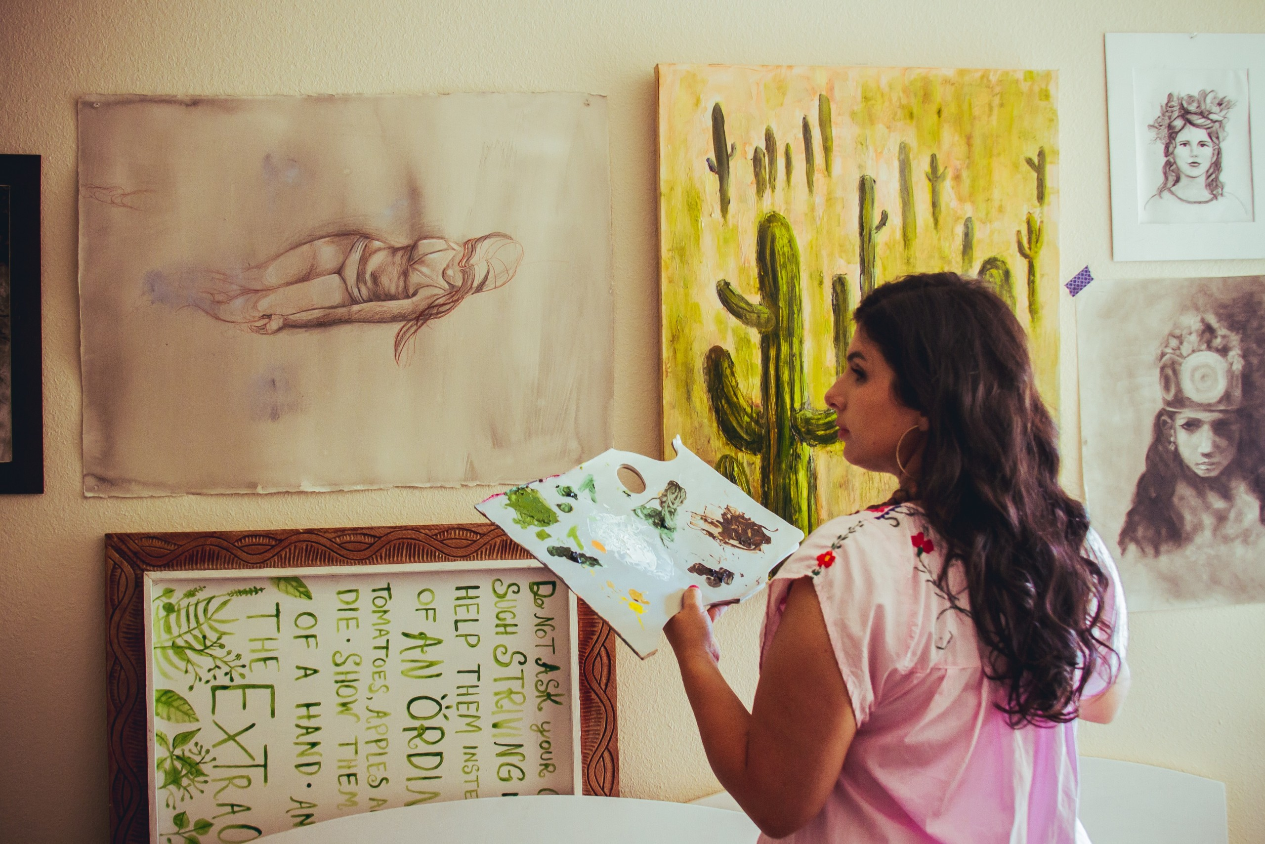 Michelle stands in front of a saguaro painting as well as some other paintings and sketches.