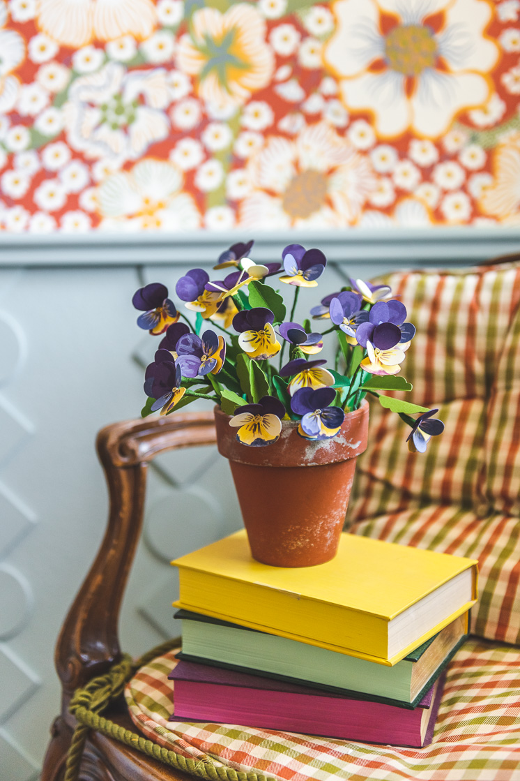 Paper pansies in a distressed terracotta planter. They're placed on a stack of colorful books on a chair. In the background, you can see some red floral wallpaper and blue wainscoting.