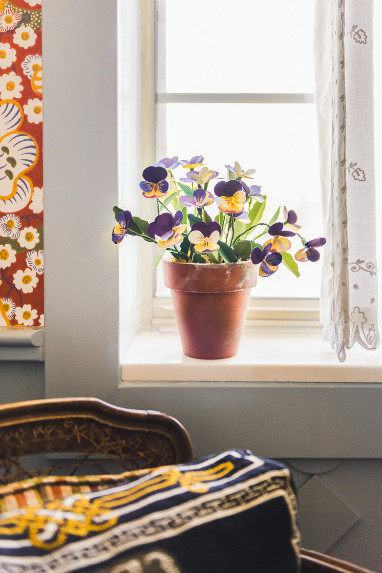 Paper pansies on a windowsill. There's a white lacy curtain next to them, and red floral wallpaper on the other.