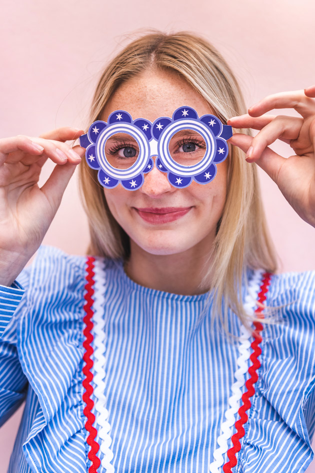 A blonde woman in a blue striped dress with red and white rick rack wears blue paper glasses with white accents in the shape of round flowers. She's standing against a blush pink background.