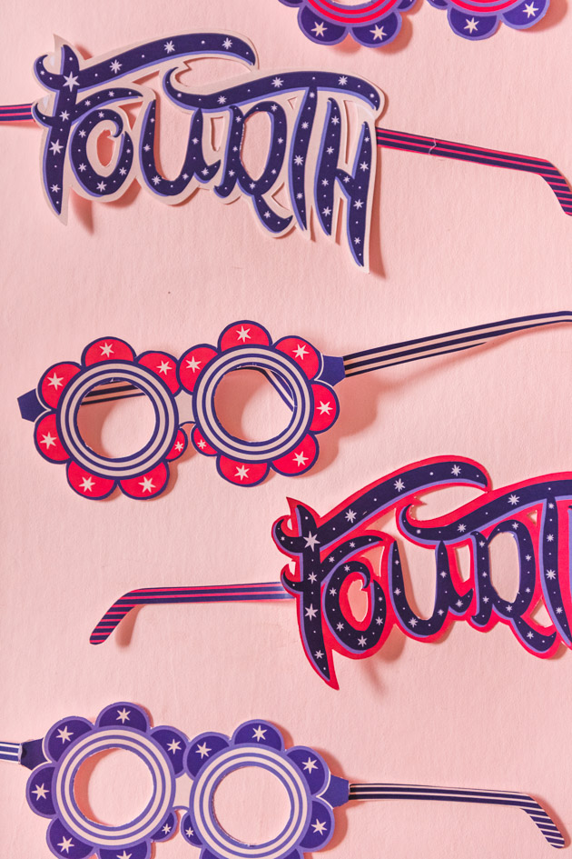 """various paper glasses, some with a round floral shape and some reading """"fourth,"""" in red and blue with white accents. They're on a blush pink background."""