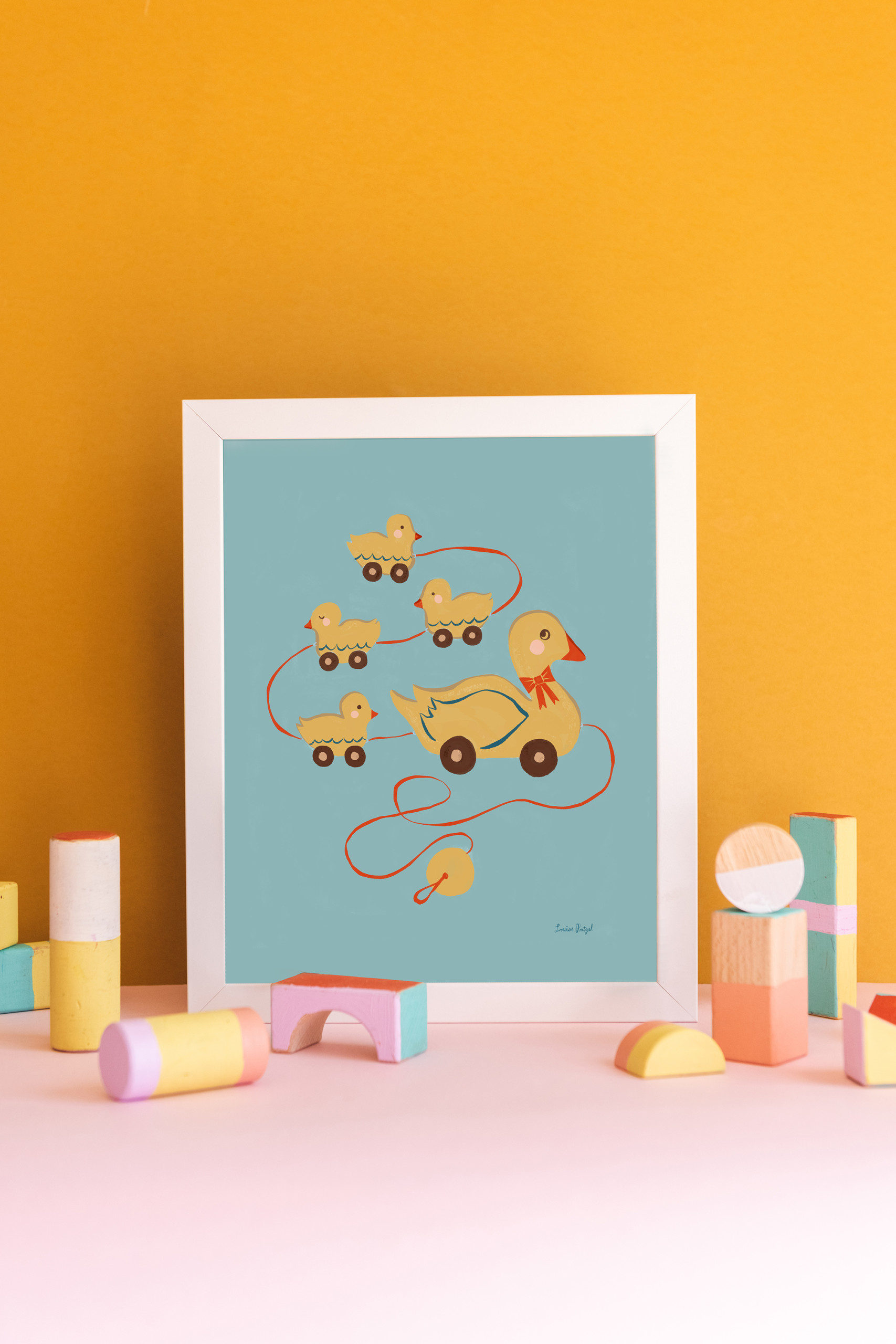 A print of Louise Pretzel's Pull Duck Toy against a gold background. Pastel wooden block toys are arranged in front.