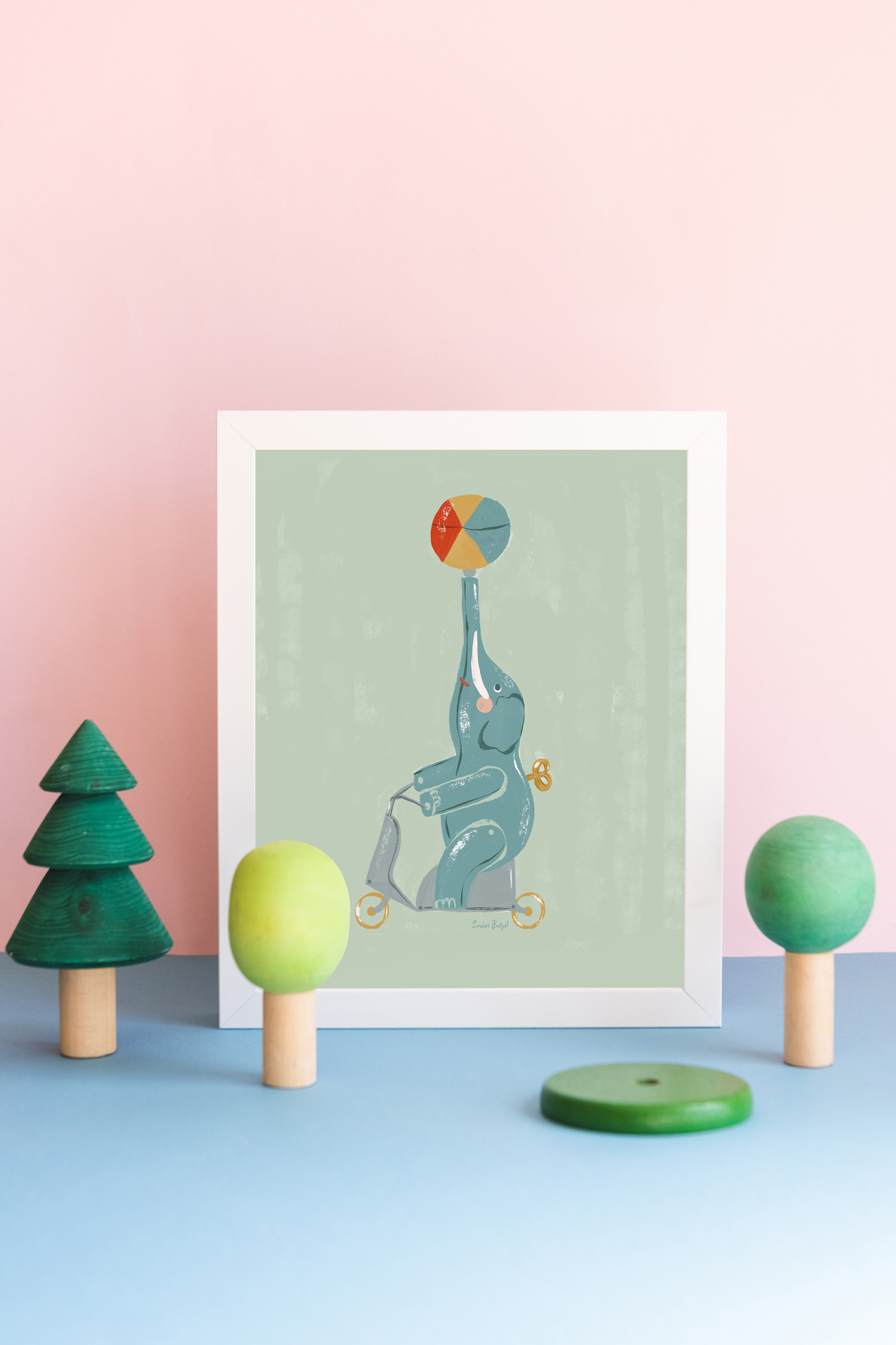 A print of Louise Pretzel's elephant leans against a pink wall with wooden tree toys in front of it.