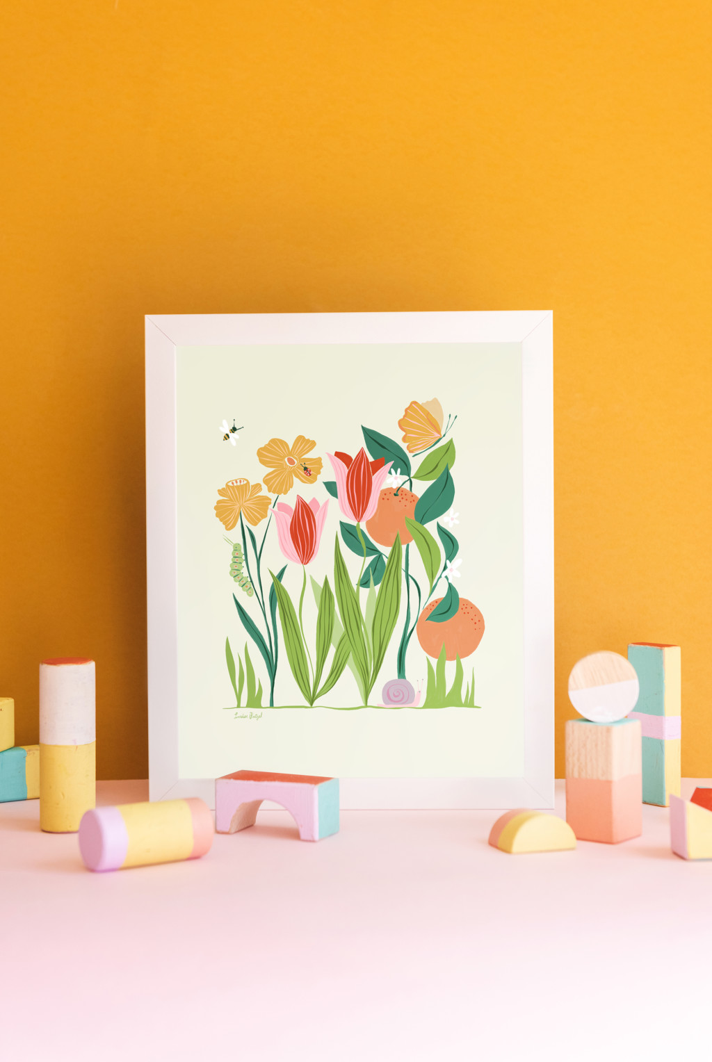 A print of Louise Pretzel's Garden leaning against a gold wall with pastel wooden blocks in front of it.