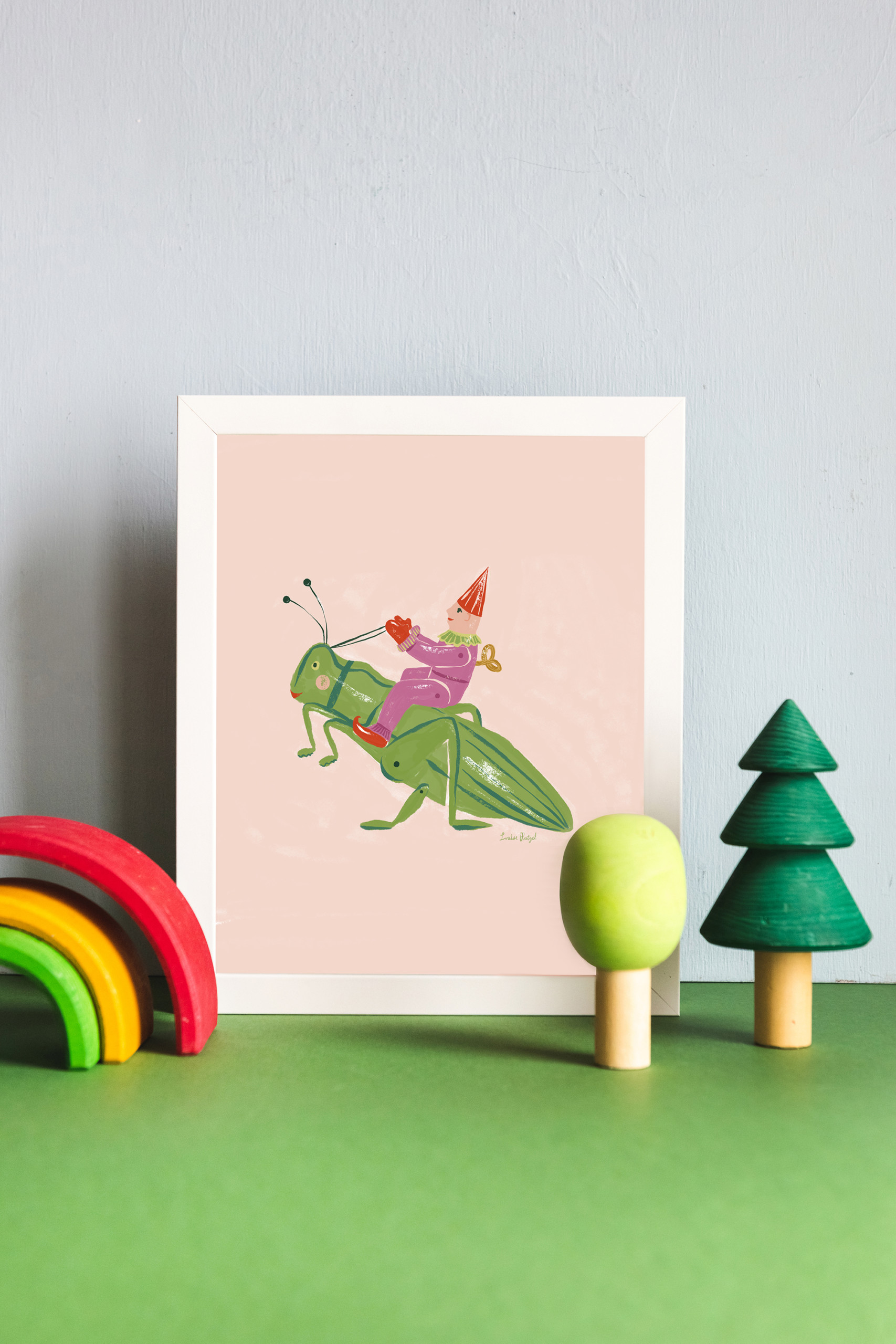 A print of Louise Pretzel's Grasshopper leaning against a light blue wall with wooden rainbow and tree toys in front of it.